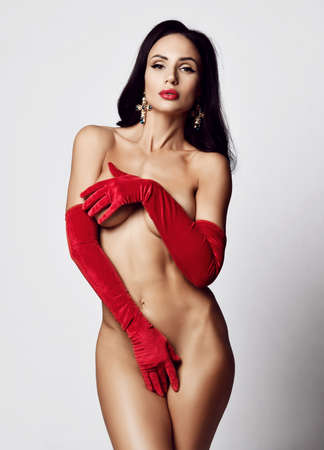 Self-confident powerful brunette woman vamp stands covering her naked body with hands in long velvet red gloves