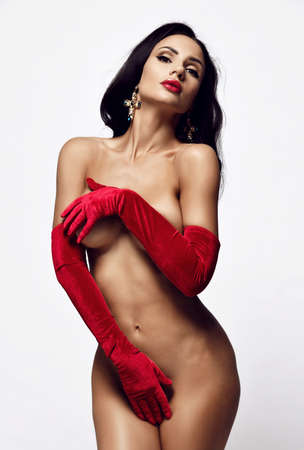 Young beautiful naked brunette woman stands covering her naked body pubis and breast with hands in long velvet red gloves