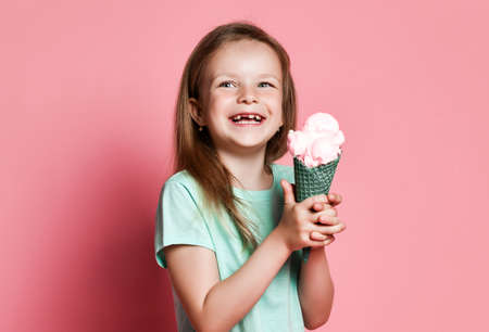 Pretty baby girl kid hold big ice cream in waffles cone with raspberry happy smiling ready to eat on pastel pink Stok Fotoğraf
