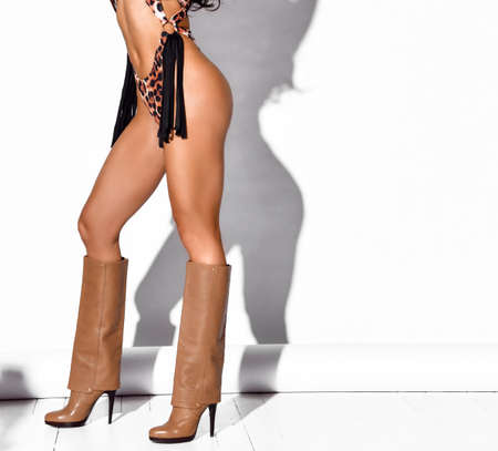 Close-up of woman legs and buttocks in sexy leopard swimsuit bikini with straps and high heel high boots