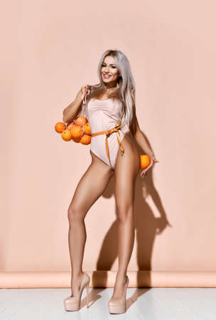 Young tall slim woman in one piece swimsuit with tape measure on waist and high heel shoes stands holding bag with oranges and one at hip. Stok Fotoğraf - 152138086