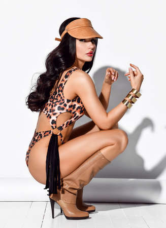 Young beautiful brunette woman in leopard swimsuit, cap, high boots, massive accessories sits squatting looks at camera over white Stok Fotoğraf - 152138087