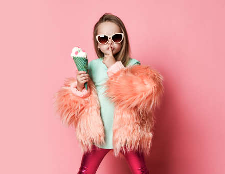Kid girl in faux fur coat and sunglasses holds big ice cream with colorful candies in waffles cone holding finger at lips gestures silence sign on pastel pink