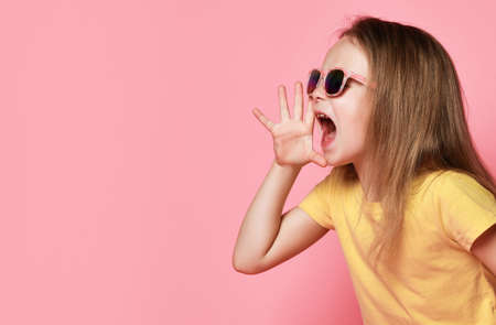 Pretty kid girl in yellow t-shirt and sunglasses holds hand at her mouth screaming saying informing loud on pastel pink Stok Fotoğraf - 152138091