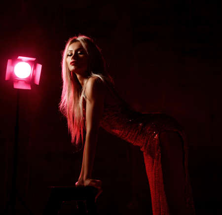 Sensual blonde woman actress in red shiny long evening dress with open legs stands leaning on chair over dark