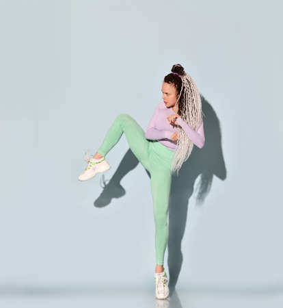 Young athletic girl with dreadlock hairstyle in tight sportswear stands holding knee up making kick by leg over light blue Stok Fotoğraf