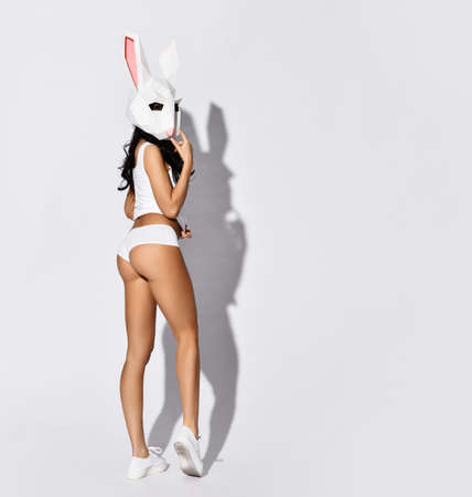 Young brunette woman in sexy white sports clothing or underwear and white rabbit mask on face stands back to camera turned head over white background with copy space. Sexy costumes concept