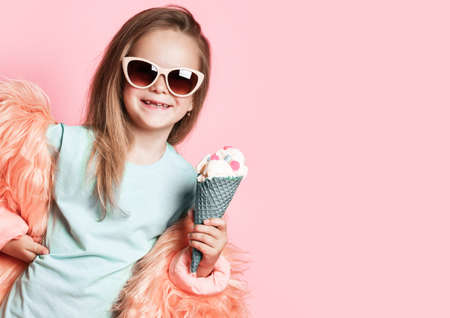 Happy smiling baby kid girl in faux fur coat and sunglasses holds big ice cream in waffles cone with colorful candies over pastel pink background with copy space