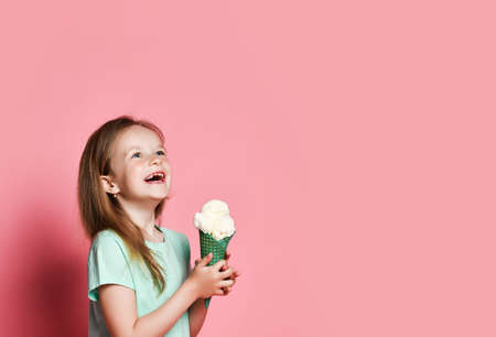 Pretty 6-7 y.o. kid girl in t-shirt holds big vanilla ice cream in waffles cone with both hands laughs looking at copy space at upper corner over pastel pink background. Side view Stok Fotoğraf - 152691260