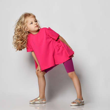 Beautiful positive little blonde girl with curly hair in stylish casual shorts and t-shirt leaning on one knee and looking aside over grey wall background. Fashion for children concept