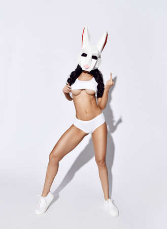 Slim brunette woman with half-naked breast in sexy white short shorts and singlet wearing rabbit mask on face standing and gestures middle fingers over white background. Sexy costumes concept Stok Fotoğraf
