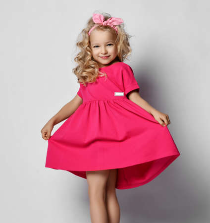 Little  blonde cute girl in beautiful pink dress with curly hair dancing posing on gray background Stok Fotoğraf - 151994617