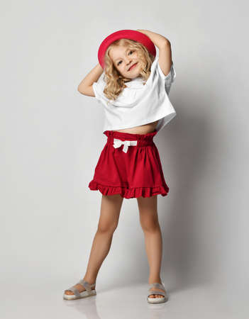 Beautiful positive little blonde girl with curly hair in stylish casual clothing, sandals and hat standing and smiling over grey wall background. Fashion for children concept Stok Fotoğraf - 151994621