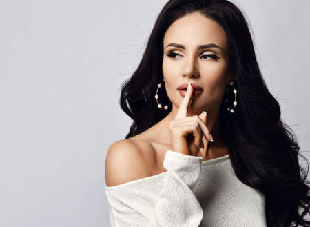 Portrait of beautiful brunette woman with long hair in one-shoulder sweater and stylish earrings looking aside holding finger at lips gesturing silence shh sign over white background. Woman beauty concept Stok Fotoğraf