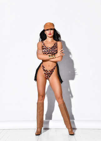 Young beautiful brunette woman in leopard bikini, cap, high boots, massive accessories stands holding arms crossed at chest over white background. Woman beauty and sexy images concept