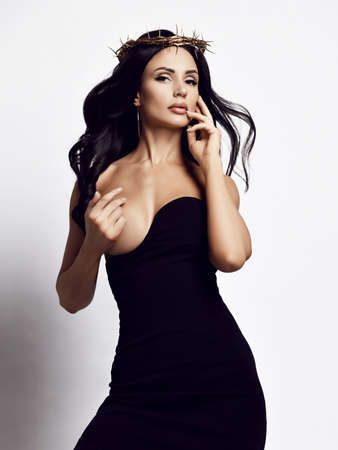 Sensual woman with long brunette hair in crown of thorns and tight dress with deep neckline stands covering her naked breast with hand over white background. Woman beauty and sexy looks concept Stok Fotoğraf