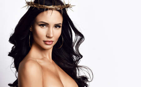 Portrait of strong powerful sensual woman with long brunette hair in crown of thorn, red pouty lips and dress with deep neckline looking at camera over white background. Woman beauty and sexy looks concept