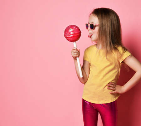 Frolic 6-7 y.o. kid girl in yellow t-shirt, shiny pink leggings and sunglasses holds big pink lollipop going to lick it over pink background with free copy space Stok Fotoğraf - 152344080