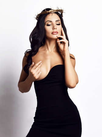 Sensual brunette woman in crown of thorns and tight dress with deep neckline stands covering her naked breast with hand and looks down over white background. Woman beauty and sexy looks concept