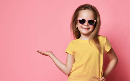 Smiling frolic 6-7 y.o. kid girl in yellow t-shirt and sunglasses holds hand up with open palm as if she holds something on it over pastel pink background with free copy space Stok Fotoğraf - 152344081
