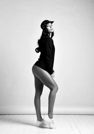 Black and white portrait of tall curvy brunette woman in jacket on naked body stylish cap sexy posing side to us demonstrating long legs and perfect buttocks. Woman beauty and sexy images concept Stok Fotoğraf - 152098953
