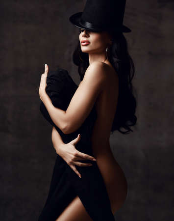 Young sensual naked woman with long brunette hair in hat stands holding clutching black clothing in hands over dark grey background. Woman beauty and sexy images concept Stok Fotoğraf - 152195275
