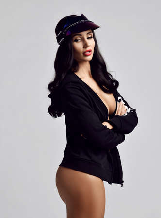 Curvy brunette woman with pouty lips wearing jacket on naked body stylish cap visor stands side to us with her arms crossed at chest over light background. Woman beauty and sexy images concept Stok Fotoğraf - 152098954
