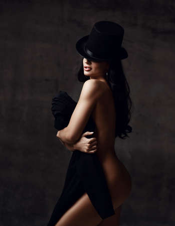Portrait of young excited sexy brunette naked woman with pouty lips and long hair in hat standing and holding black clothing in hands over dark grey background. Woman beauty and sexy images concept Stok Fotoğraf - 152195276