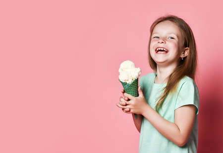 Happy laughing 6-7 y.o. girl kid in white t-shirt eats big vanilla ice cream in waffles cone over pink background with copy space. Side view Stok Fotoğraf - 152344082