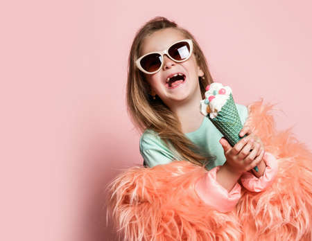 Frolic kid girl in faux fur coat holds with both hands big ice cream in waffles cone decorated with colorful candies and happy laughs over pastel pink background with copy space