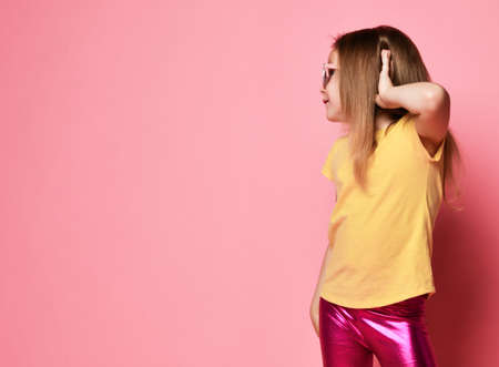 Frolic 6-7 y.o. slim kid girl in yellow t-shirt, shiny pink leggings and sunglasses holds hand at her ear to hear better head turned to copy space on pastel pink background Stok Fotoğraf - 152422391