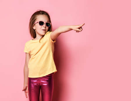 Surprised amazed frolic 6-7 y.o. kid girl in yellow t-shirt, shiny glossy pink leggings and sunglasses pointing finger at copy space on pastel pink background Stok Fotoğraf