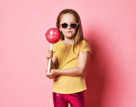 Frolic 6-7 y.o. kid girl in yellow t-shirt, shiny pink leggings and sunglasses holds big heavy pink lollipop satisfied smiling over pink background