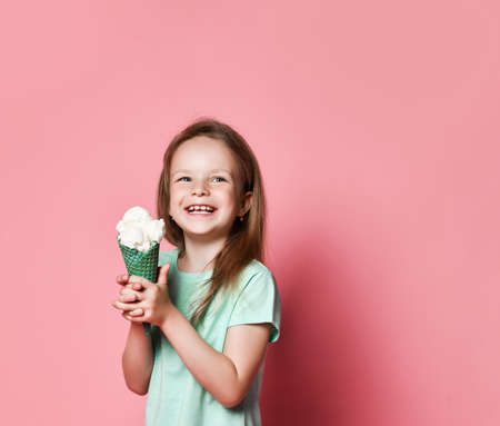 Pretty baby girl kid hold big ice cream in waffles cone with raspberry happy smiling ready to eat looks at copy space upper corner on pastel pink background Stok Fotoğraf - 152422395