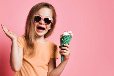 Frolic kid girl preschooler in t-shirt and sunglasses with big vanilla ice cream with candies in waffles in her hand laughs and holds hand up with open palm over pink background with copy space