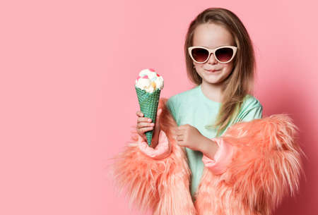 Glad and smiling stylish rich kid girl in faux fur coat and sunglasses holds big ice cream with candies in waffles cone on pastel pink background with free copy space Stok Fotoğraf - 152422399