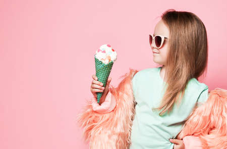Rich stylish kid girl in faux fur coat and sunglasses pleased looks at big ice cream with candies in waffles cone she holds on pastel pink background with free copy space Stok Fotoğraf - 152422401