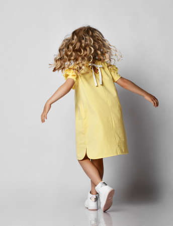 Little blonde curly girl in yellow dress and sneakers moving over grey wall background, rear view. Stylish casual fashion for children Stok Fotoğraf - 152316841