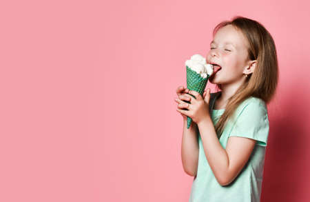 Happy 6-7 y.o. girl kid in white t-shirt licks eats big vanilla ice cream in waffles cone with closed of pleasure eyes over pink background with copy space. Side view