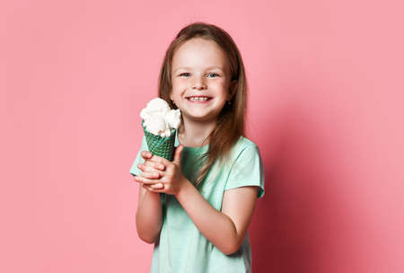 Portrait of frolic pretty kid girl in t-shirt holding going to eat showing big vanilla ice cream in waffles cone on pastel pink background Stok Fotoğraf - 152422402