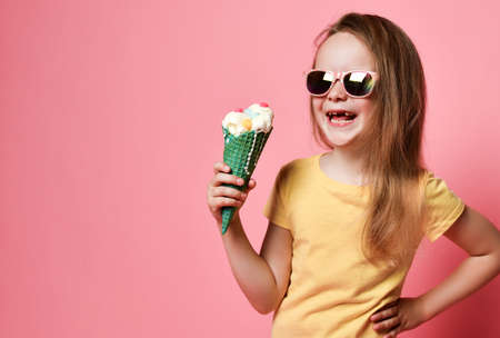 Happy laughing frolic kid girl in yellow t-shirt and sunglasses holds big vanilla ice cream with candies in waffles cone over pink on pastel pink background with copy space Stok Fotoğraf - 152422404