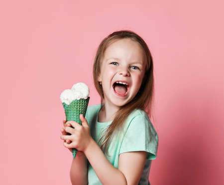 Frolic happy screaming 6-7 y.o. girl kid in white t-shirt holds with both hands eats big vanilla ice cream in waffles cone over pink background Stok Fotoğraf - 152422405
