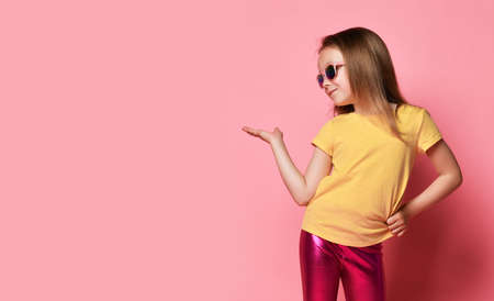 Smiling 6-7 y.o. kid girl in yellow t-shirt, glossy legging and sunglasses holds and looks at her hand up with open palm as if she holds something on it over pink background with free copy space Stok Fotoğraf