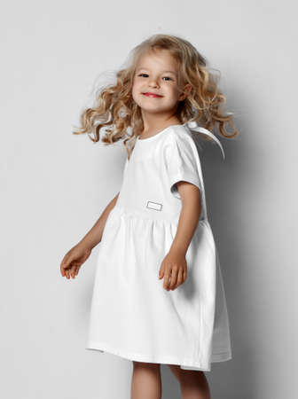 Little blonde curly positive princess girl in white casual dress and sneakers standing walking with curly hair over grey wall background. Stylish comfortable everyday fashion for children concept Stok Fotoğraf - 152775092