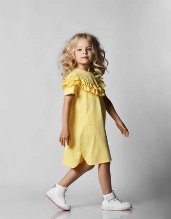 Little blonde curly positive princess girl in yellow casual dress and white sneakers standing walking  over grey wall background. Stylish comfortable everyday fashion for children concept