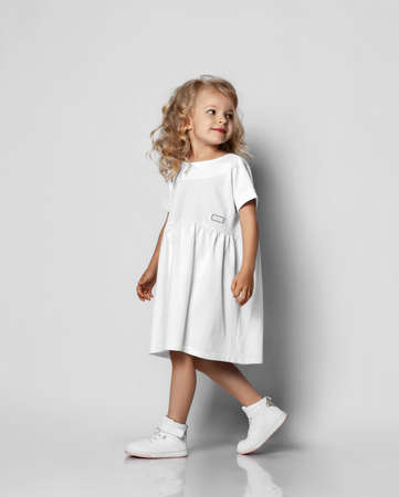 Little blonde curly positive princess girl in white casual dress and sneakers standing walking with curly hair over grey wall background. Stylish comfortable everyday fashion for children concept