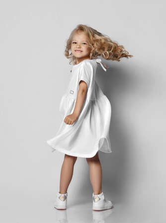 Little blonde curly positive princess girl in white casual dress and sneakers standing walking with curly hair over grey wall background. Stylish comfortable everyday fashion for children concept Stok Fotoğraf - 152729303