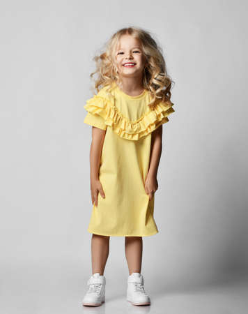 Little blonde curly positive princess girl in yellow casual dress and white sneakers standing walking  over grey wall background. Stylish comfortable everyday fashion for children concept Stok Fotoğraf - 152729318