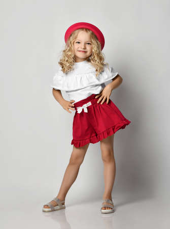 Beautiful positive little blonde girl with curly hair in stylish casual clothing, sandals and hat standing and smiling over grey wall background. Fashion for children concept Stok Fotoğraf - 152784709