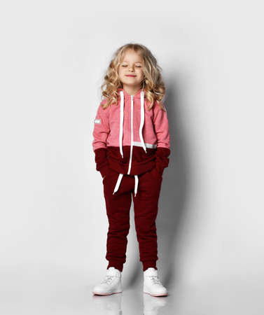 Little blonde curly beautiful girl in red sport costume and white sneakers standing walking with hands in pockets over grey wall background. Stylish casual fashion for children concept